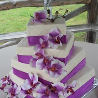 Laurae 4 offset square quilted tiers wrapped in Orchid ribbon and artificail orchids