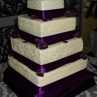 Purple Wedding! Traditional white-on-white wedding cake, WASC with vanilla buttercream! Piping in buttercream, roses and leaves made from modeling...