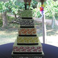 Bobble Head Cake Five tiered, square cake, edged with black ribbon. Each layer's color of decorations represented a bridal attendant's dress color...