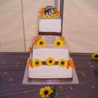 Sunflower Wedding Cake 3-tier fondant ivoyr wedding cake with brown fondant trim. Sunflower and Alstromeria gumpaste flowers.