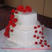 Hexagon Rose Wedding Cake White hexagon fondant wedding cake. Med and Lrg gumpast roses on Jage green ivy on the left and small royal icing roses on the right.