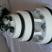 Black & White Bow   Chocolate, vanilla & orange sponges. Iced in fondant & gumpaste with petal paste roses.