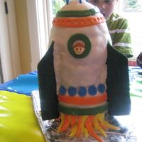 Space Rocket Cake  This is a 7 layer, stacked cake with a thin dowel running through the bottom five layers for support. I used a Rolled Buttercream Icing...