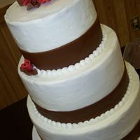 Megan's Chocolate And Crimson 10, 8, 6 white cake with BC icing. Chocolate fondant ribbon, and fondant roses. First 3 tiered cake... your thoughts or suggestions welcome...