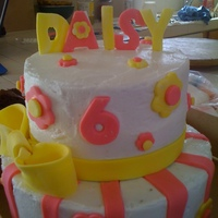 Daisy's 6Th Birthday 2 tiered cake frosted in buttercream with fondant accents