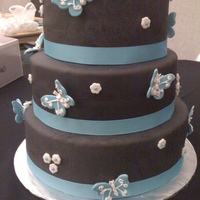 Smith Wedding 3 tiered round wedding cake covered in fondant. Butterflies made from fondant, detail work done with royal icing.
