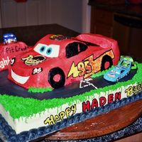 Lighting Mcqueen Racing Used Wilton Car pan and added ricecrispy treats to help shape car on top of a sheet cake. Buttercream with some fondant accents. The 4...