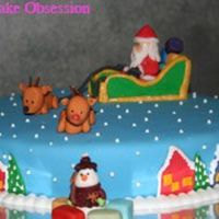 Santa And His Sleigh Christmas Cake Chocolate cake frosted with chocolate buttercream and covered in fondant. All decorations are made in fondant except for the snowman which...