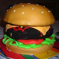 Burger french vanilla bun covered in MMF; chocolate patty covered in chocolate frosting and oreo crumbs; MMF lettuce, tomato, and cheese; frosting...