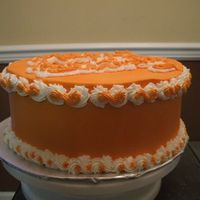Orange   A dummy cake with orange and white buttercream decorations.