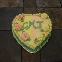 Yellow/orange Heart  Heart shaped cake with buttercream frosting and gumpaste flowers and royal icing momongram and fondant leaves on the side (cannot be seen...