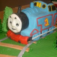 Thomas The Train   Thomas was made for a 4th birthday. He was sculpted out of fondant that was dyed to the corresponding colors.