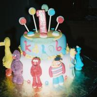 Sesame Street Characters were made of fondant.Cake was covered with satin ice fondant. Cake inside was strawberry. I dyed the cake different colors for a...