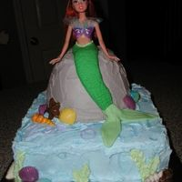 "Ariel Birthday Cake An actual Ariel doll is sitting in a bowl cake. The doll was longer, so her feet are also going into the 10"" square cake. The cake is..."