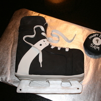 Hockey Skate White cake covered with fondant. Laces and blade are made of fondant also. Blade is painted silver.