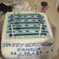 Swimming Pool Cake Made for a lady on my swim team. Covered in Buttercream, used Fondant for flags and lanes, used piping gel w/ blue coloring for water.