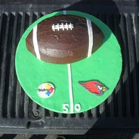 Super Bowl Cake  WASC cake filled and iced with ganache. fondant accents. took the pic on the tailgate of DH truck...thought it was appropriate for football...