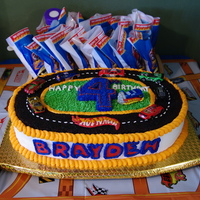 "Hot Wheels Party Cake Cake is 2 - 12"" layers, split & 2 - 9x13"" layers trimmed to form oval track. ""Asphalt"" is made from chocolate..."