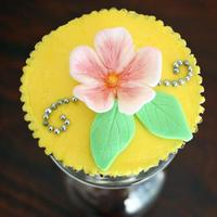 Yellow Flower Cupcake Buttercream icing topped with a fondant flower, leaves and silver cachous