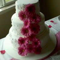 Pink Daisy Wedding 3 Tier cake, covered in white fondant. Real pink daisies adorn the front in a cascade pattern. Small white daisy cutouts are placed on each...