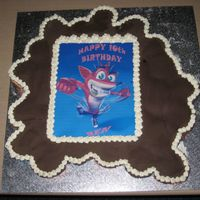 Crash Bandicoot Cupcake Cake Blue and orange wrapped chocolate cupcakes sitting under chocolate fondant with edible crash bandicoot picture and writing done on...