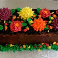 Wooden Basket Of Fall Flowers   chocolate fudge cake with white chocolate icing and roayl icing leaves and flowers, leaf sprinkles and grass. Crushed oreos as dirt.