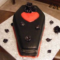 Coffin With Black Sugar Roses chocolate fudge cake filled with raspberry filling and coated with dark chocolate fondant and then painted in black disco dusts with a...