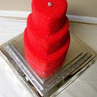 Glitter Me Red In Luv! Red satin ice fondant crusted in pink and red americolor sanding sugars, stacked heart in 6, 9, 12 inch cakes.Silver dragees down front and...