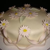 Mini Daisies I created this cake using MMF and gum paste flowers. Any comments are greatly appreciated.