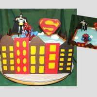 "Super Hero Birthday Cake Choc cake with raspberry filling (yum!). BC frosting with chocolate transfer buildings and superman ""s."" Batman was a toy and..."