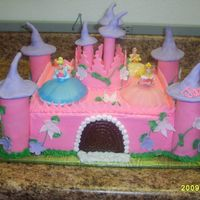 Princess Castle Square Cake , Iced in pink , parts of castle made with foundant . Flowers also made with fondant with the 3 princess on top.