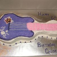 Hannah Montana Guitar Cake Wilton guitar pan, star tipped purple and pink icing to outline guitar. Made cupcakes in pink and purple swirl to go with this.
