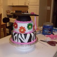 Grad Cake With Cap, Daisies, And Zebra Pattern, First Fondant Cake This is my FIRST fondant, tiered cake, and first time using gum paste. This was for my sisters graduation party. Everything is fondant...