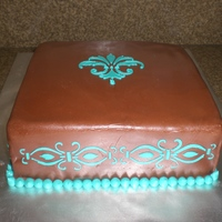 Fleur De Lis Chocolate Fondant with turquoise royal icing stenciled on cake. Cake was triple chocolate with caramel filling.