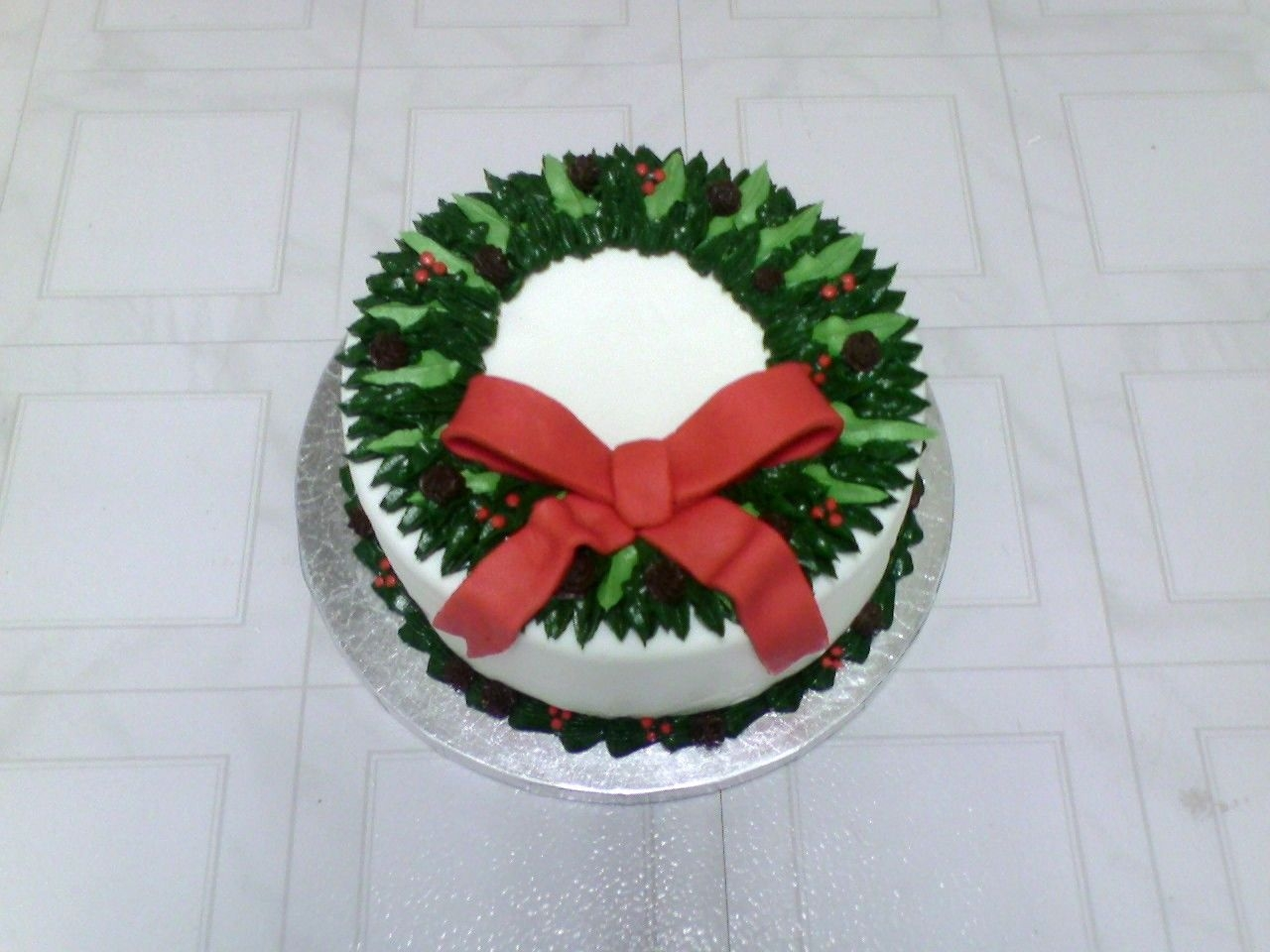 Holiday Wreath Cake White MMF w/buttercream greenery, pine cones and holly, fondant bow. I would change a few things next time.