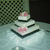 Quilted Wedding Cake French Vanilla with custard filling, buttercream icing, black satin ribbon border, dragees in the crosshatches of the quilting. Silk...