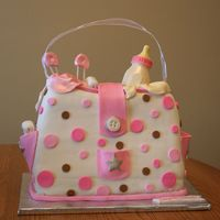 Pink Diaper Bag Shower Cake It's a Girl Baby Shower Cake, inspired by Cake Girls. Covered in fondant, fondant decorations, chocolate bottle.