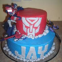 "Transformer Cake  This was my little boy's 6th birthday cake. 2 tier (10'' & 8"") All buttercream except the autobot face, letters,..."