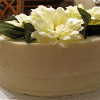 Flowers & Lace Cake This is an 8'' Double Layer Vanilla Buttercream covered Butter Pecan Rum Cake.The top has faux flowers & leaves with a lace...