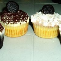 Black & White Cupcakes In detail: (from left to right) Chocolate cupcake with vanilla frosting, vanilla cupcake with vanilla frosting, both are topped with...