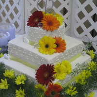 "Gerbera Daisy Wedding Cake 16"" square, 12"" square, 8"" round. Yellow cake, buttercream frosting. Live flowers."