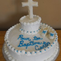 Baptism Cake   Chocolate cake with buttercream and cross and booties are modeling chocolate .