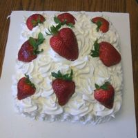 Mile High Strawberries And Cream french vanilla cake filled with pastry cream and fresh strawberries,iced with whipped cream and garnished with fresh berries.