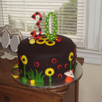 "Black Celebration Cake 3 layer 12"" round with Bumble Bee, Lady Bug and Toadstools2 layers of vanilla cake, 1 layer of chocolate with vanilla buttercream..."