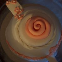 Peach Fondant Ribbon Rose A close up of the fondant ribbon rose on top of the peach teapot cake.