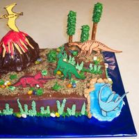 Dinosaur Cake  Chocolate cake with buttercream icing. I used a design by DianeLM. Mine is a sad version of hers, but my son loved it! The dinosaurs are...