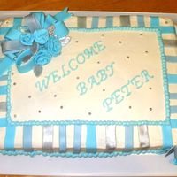 Cakes_065Crop.jpg Baby shower cake for a co-worker. Chocolate cake with buttercream icing. Flowers and ribbon and side accents are fondant, some painted...