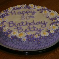 Floral Birthday Cake a white confetti cake with buttercream frosting and royal icing flowers lining the edges. It was done in different shades of lavender.