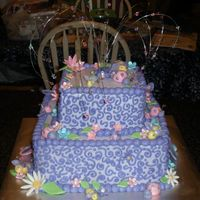 Baby Girl Bug Cake This is a two tier cake with buttercream icing. I made the flowers and bugs by hand from fondant and brushed them with pearl lusterdust...