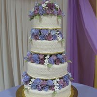 Img_1058_2.jpg 4 tiers wedding cake ivory fondant quilted with ivory pearls, roses blue and purple
